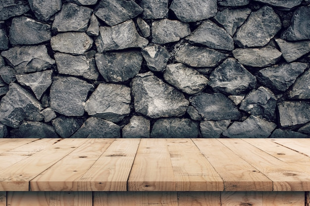 Il fondo della parete di pietra e la tavola di legno vuota visualizzano il montaggio per il prodotto con lo spazio della copia.