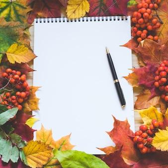 Il fondo di tema di autunno con le foglie di acero, lo spazio in bianco vuoto e la penna per scrivono.