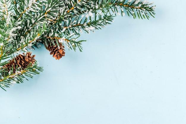 Il fondo leggero del nuovo anno e di natale, il concetto della cartolina d'auguri, i rami dell'albero di natale con le pigne e la neve artificiale, vista dall'alto copiano lo spazio