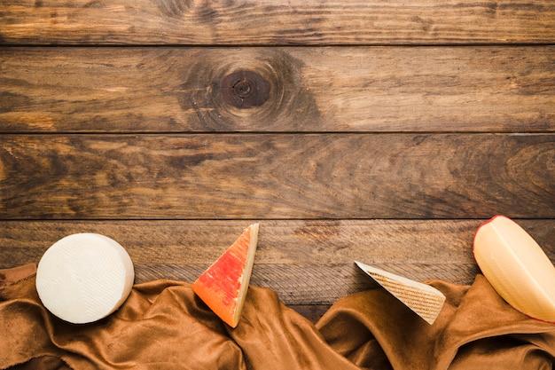 Il formaggio organico ha sistemato in una fila con tessuto marrone sulla tavola di legno