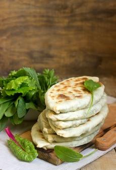 Il fornaio che prepara piatti tradizionali armeni dai cappelli artsakh zhingyalov è un tipo di focaccia farcita con erbe.