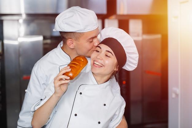Il fornaio del ragazzo bacia una ragazza sulla guancia in una panetteria sullo sfondo del forno.