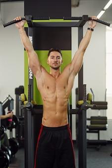 Il forte uomo attraente tira su la traversa durante l'allenamento nella moderna palestra. vista frontale.