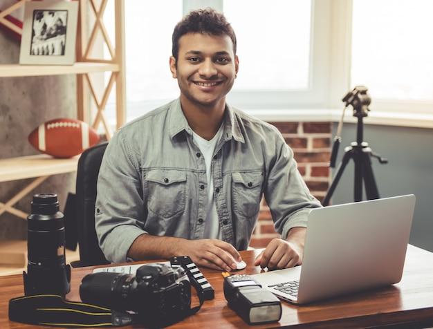 Il fotografo afroamericano attraente sta esaminando la macchina fotografica.