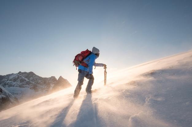 Il fotografo dell'uomo con il treppiede sta scalando sulla collina del pendio con blizzard