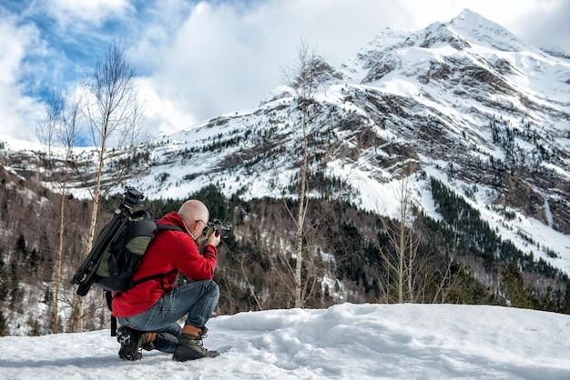 Il fotografo dell'uomo scatta foto tra le montagne innevate