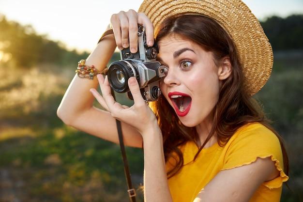 Il fotografo della donna esamina l'obiettivo della macchina fotografica con la natura sorpresa di sguardo sorpresa della bocca aperta.