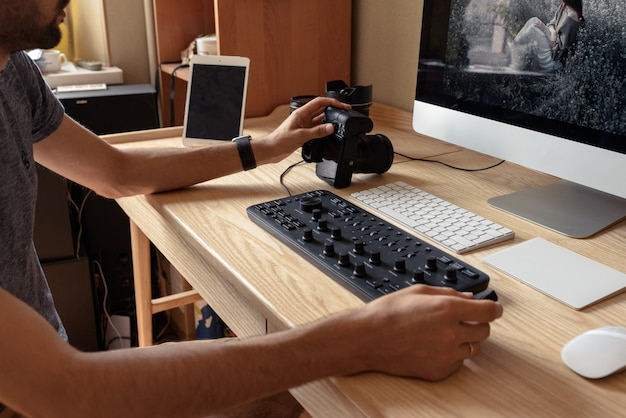 Il fotografo elabora le foto su un computer a un tavolo in una stanza