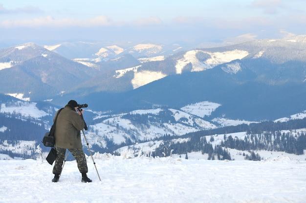 Il fotografo scatta foto dalla cima della montagna