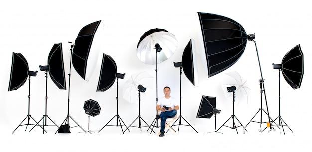 Il fotografo si siede sulla sedia del regista con luci da studio flash