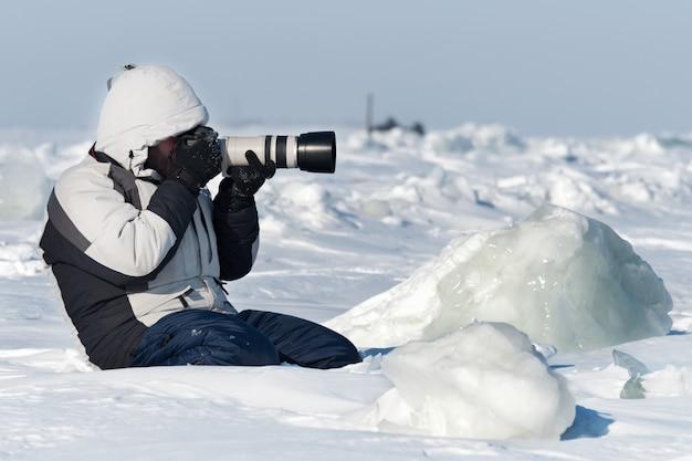Il fotografo sta fotografando con il teleobiettivo nel ghiaccio artico.