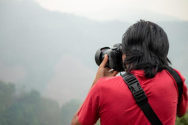 Il fotografo sta fotografando la montagna durante i suoi viaggi.