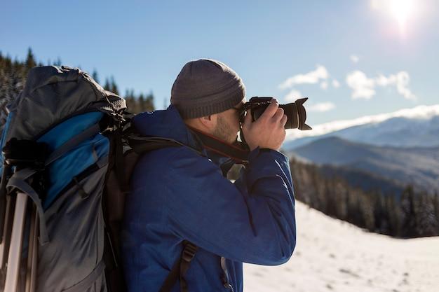 Il fotografo turistico dell'uomo della viandante in abbigliamento caldo con lo zaino e la macchina fotografica che prendono l'immagine della valle nevosa e le cime boscose abbelliscono sotto cielo blu il giorno soleggiato del freddo dell'inverno.
