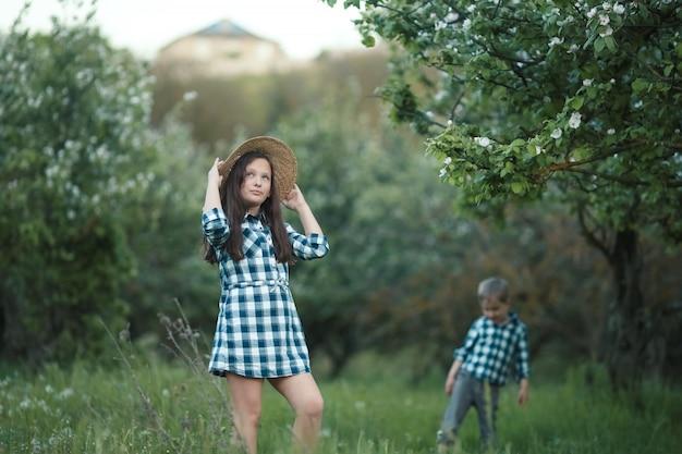 Il fratello e la sorella dell'età scolare camminano nel giardino verde sull'erba del prato inglese