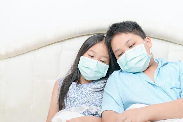Il fratello e la sorella indossano la maschera chirurgica sedersi sul letto, bambino malato
