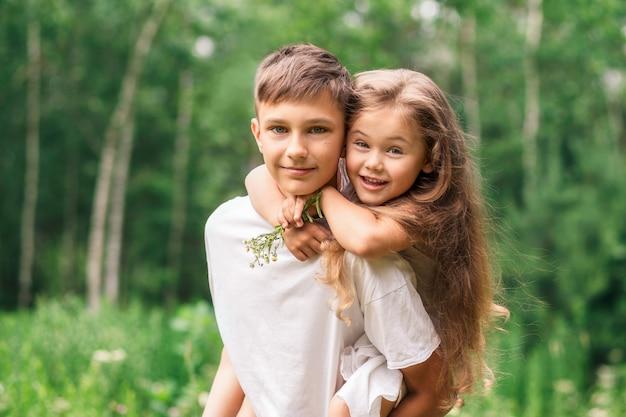 Il fratello tiene la sorella sulle spalle all'aperto in estate