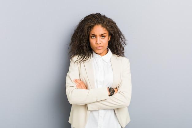 Il fronte aggrottante le sopracciglia della giovane donna di affari dell'afroamericano nel dispiacere, tiene le braccia piegate.