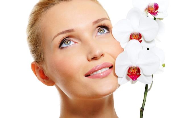 Il fronte della bella donna sorridente con il fiore bianco fresco dell'orchidea