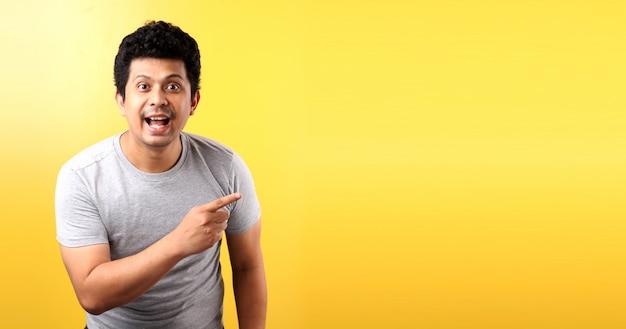 Il fronte di scossa e sorpresa dell'uomo asiatico indica su spazio vuoto isolato sulla parete gialla.