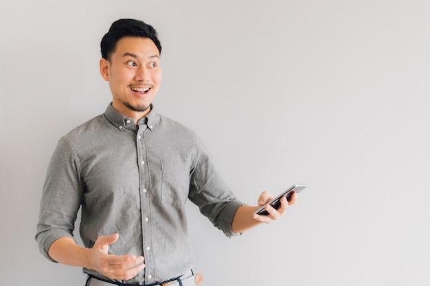Il fronte felice e wow dell'uomo asiatico utilizza lo smartphone su fondo grigio isolato