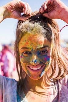 Il fronte sorridente della giovane donna coperto di colore di holi che esamina la macchina fotografica