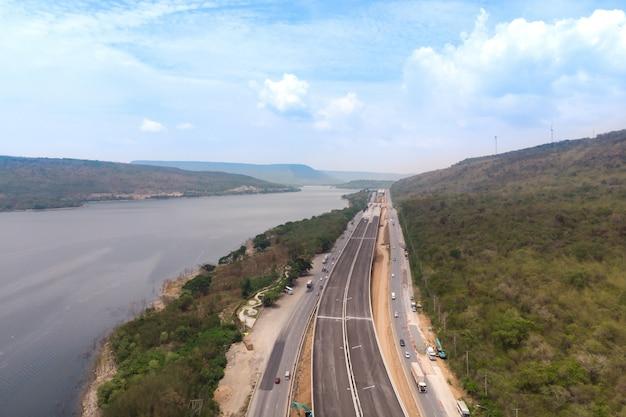 Il fuco ha sparato il paesaggio di vista aerea dei pedaggi autostradali in costruzione vicino al grande fiume naturale