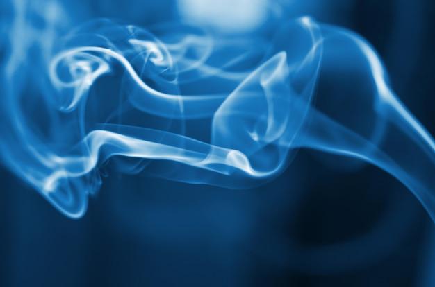 Il fumo dell'incenso si attacca. arte astratta. focalizzazione morbida. colore dell'anno 2020 blu classico.