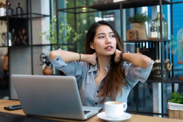 Il funzionamento asiatico della donna e beve il caffè in caffè con il sorriso del computer portatile e il lavoro felice