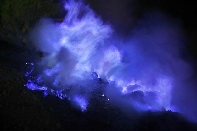 Il fuoco blu nella nebbia di notte sul vulcano ijen, indonesia