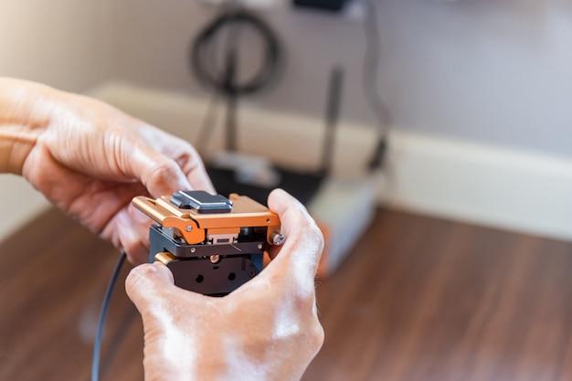 Il fuoco selettivo dell'uomo dei tecnici di internet sta tagliando i cavi a fibre ottiche con l'utensile da taglio prepara per la giunzione, rete domestica di it