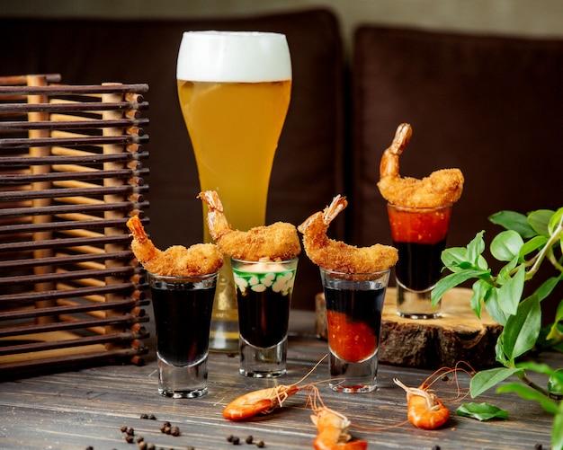 Il gambero fritto croccante è servito sopra i bicchierini riempiti di salse