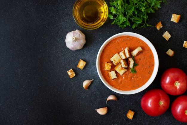 Il gazpacho freddo tradizionale della minestra del pomodoro dell'estate è servito in una ciotola bianca. pomodori, aglio, basilico, prezzemolo, olio d'oliva e crostini. cucina mediterranea, spagnola. vista dall'alto. sfondo nero. copia spazio