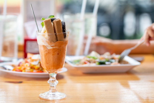 Il gelato della parfait della vaniglia con il wafer in un vetro è servito sullo scrittorio di legno in mensa della asia