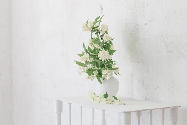 Il gelsomino fiorisce in vaso sulla vecchia parete del fondo