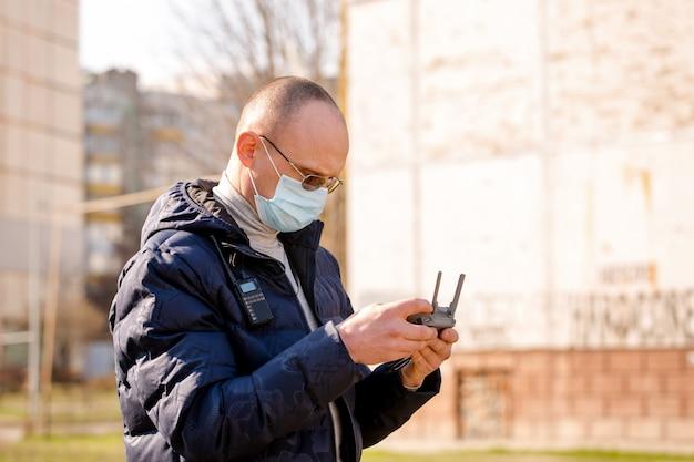 Il geometra in una maschera protettiva controlla un quadrocopter