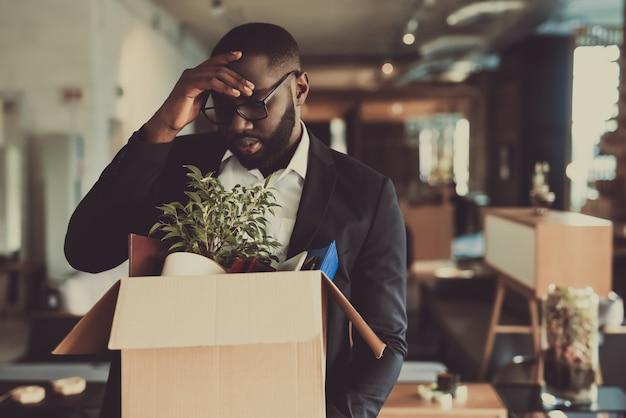 Il gestore nero lascia il lavoro con la scatola dell'ufficio
