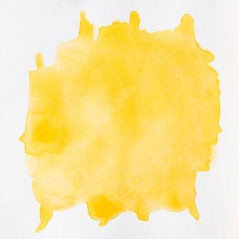 Il giallo liquido dell'acquerello spruzza su fondo bianco