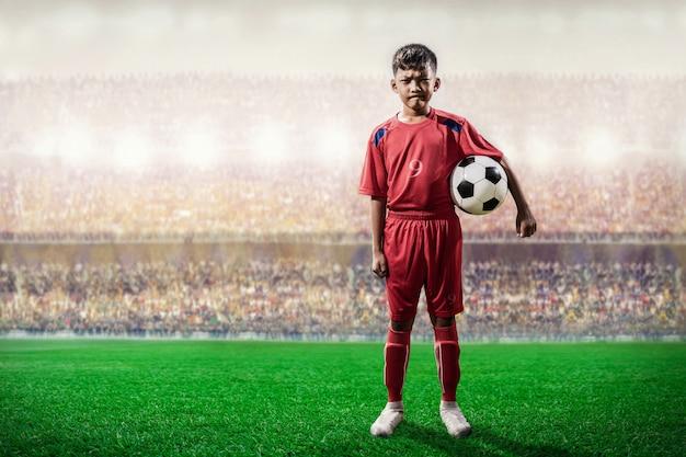Il giocatore asiatico dei bambini di calcio nella condizione della jersey rossa e posa alla macchina fotografica nello stadio
