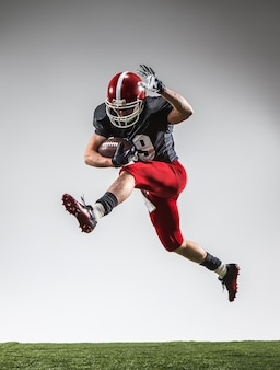 Il giocatore di football americano in azione su erba verde e sfondo grigio.