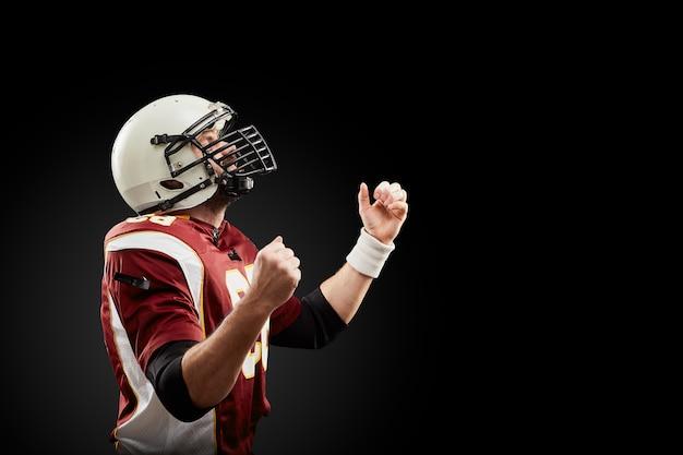 Il giocatore di football americano isolato si rallegra nella vittoria in parete nera