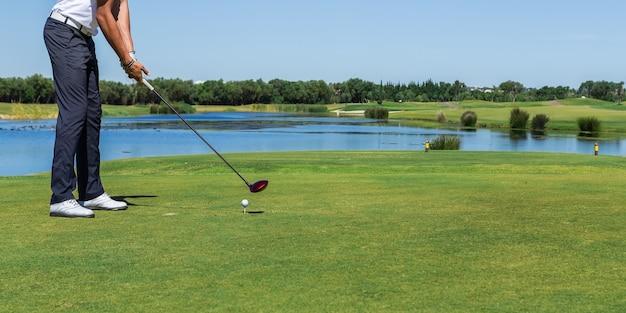 Il giocatore di golf maschio ha colpito la palla con il bastone