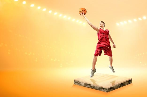 Il giocatore di pallacanestro asiatico dell'uomo con la palla salta nell'aria