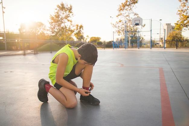 Il giocatore di pallacanestro del giovane sta legando i lacci delle scarpe