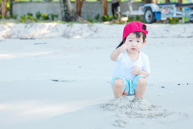 Il gioco asiatico sveglio del bambino del primo piano con la sabbia su spiaggia ha strutturato il fondo