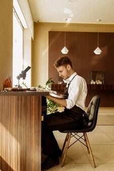 Il gioielliere considera il catalogo dei prodotti seduti sul posto di lavoro