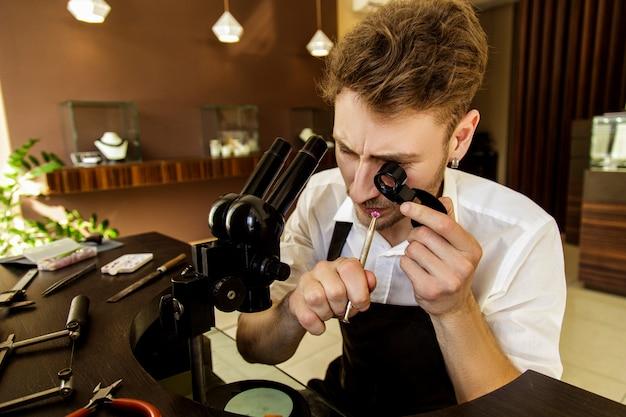 Il gioielliere esamina la gemma sotto la lente d'ingrandimento