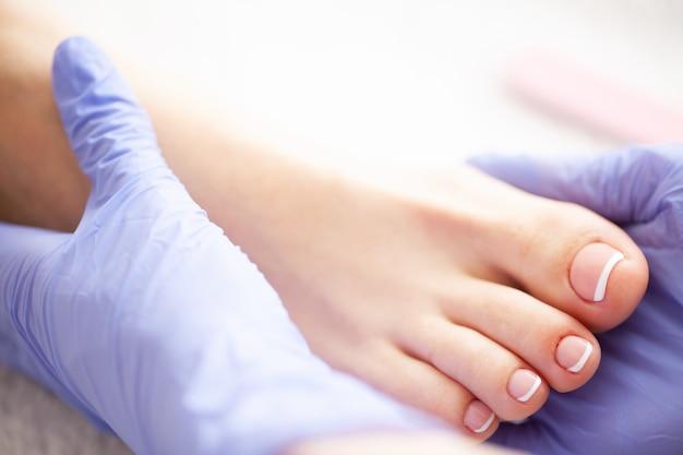 Il giorno della pedicure. lo specialista in pedicure lavora con il paziente nel salone spa