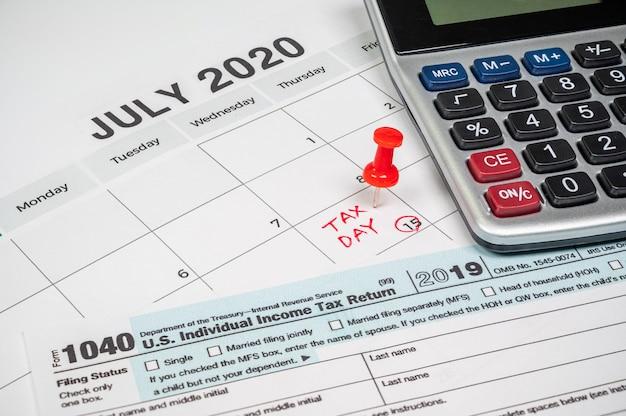 Il giorno delle tasse fu esteso al 15 luglio a causa di covid-19. calendario di luglio con modulo di reso 1040 e giorno fiscale.
