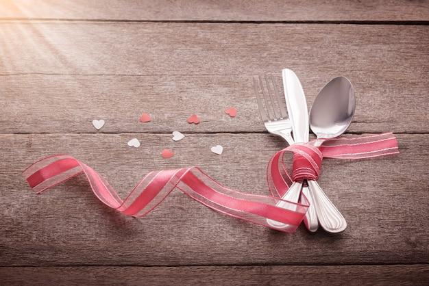 Il giorno di biglietti di s. valentino ha messo con argenteria e cuore su di legno