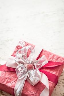 Il giorno di san valentino e la festa della mamma, confezione regalo rossa con fiocco e rose su fondo in legno chiaro